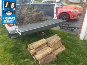 Silverado LTZ truck bed load of dirt and logs