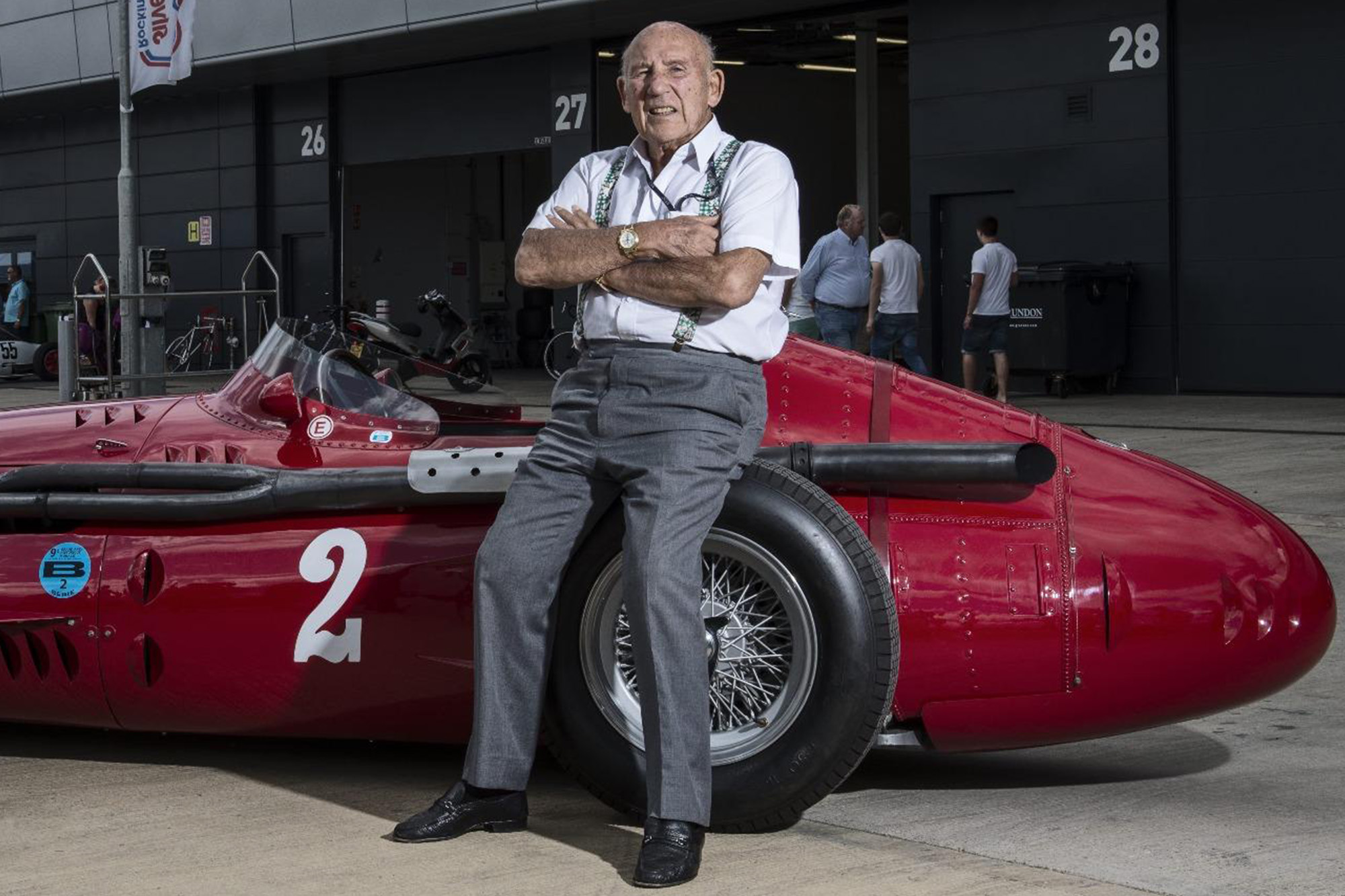 Sir Stirling Moss Leans on Racecar Wheel