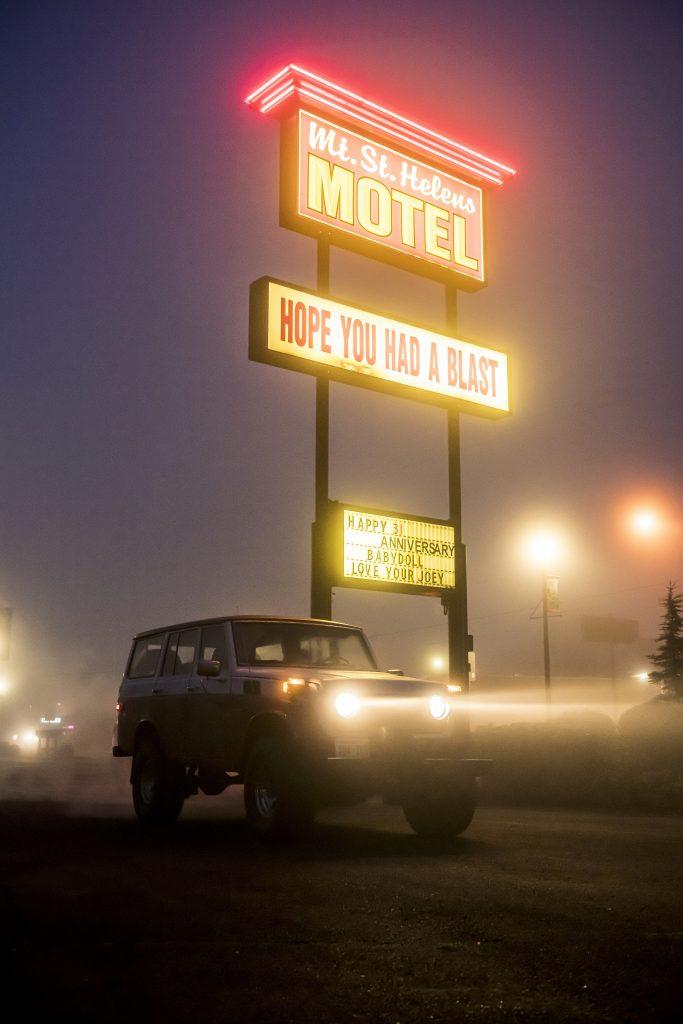FJ55 Land Cruiser Beside Neon Hotel Sign In Evening