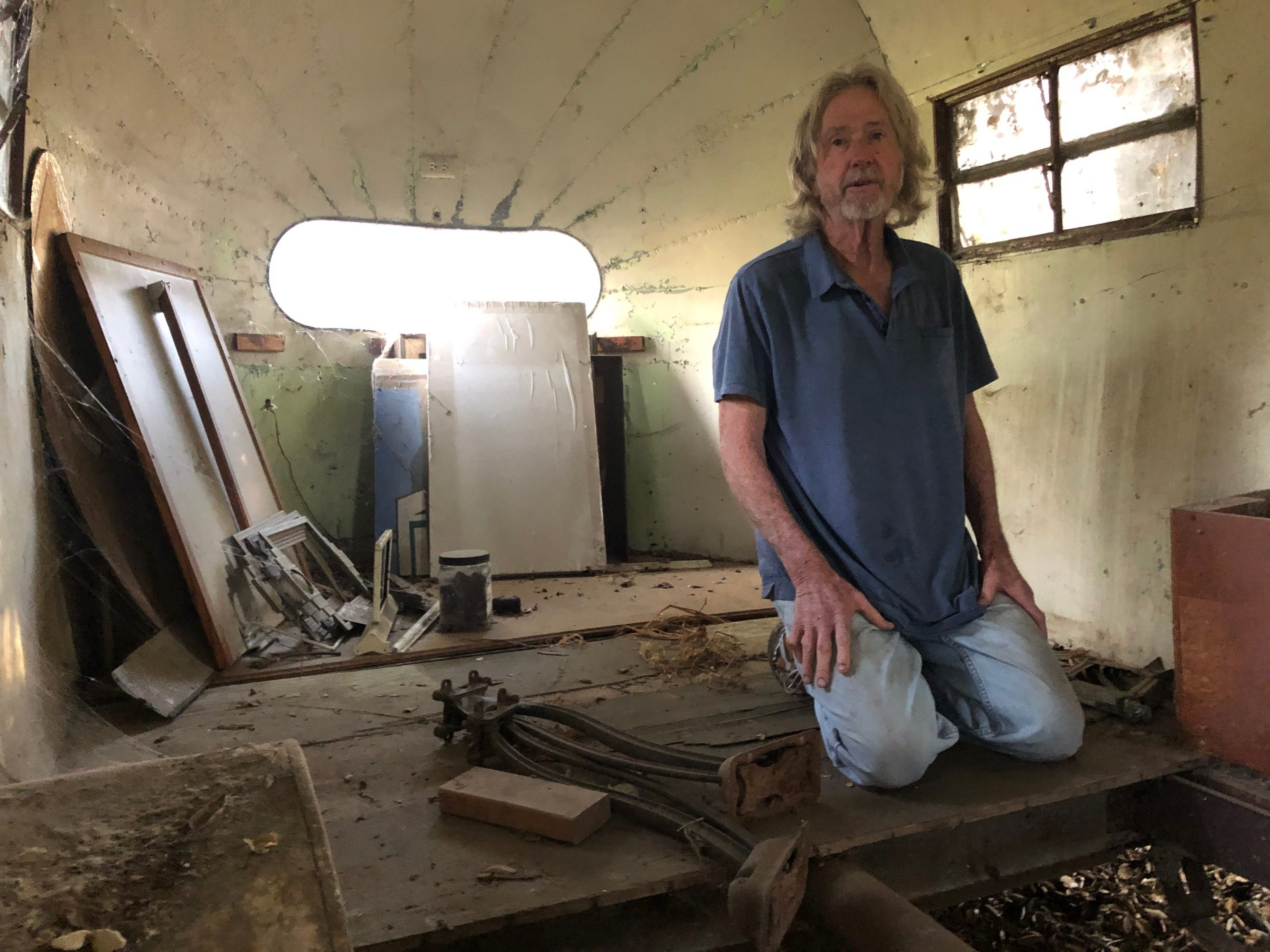 tom donahue kneels inside of vintage airstream shell