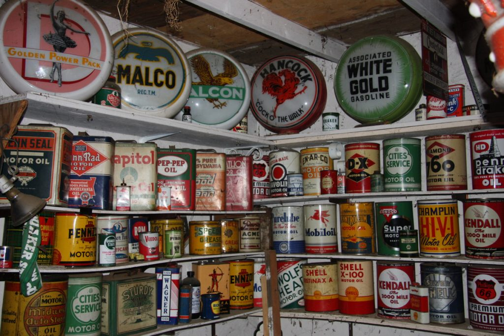 vintage oil cans and signs on shelves