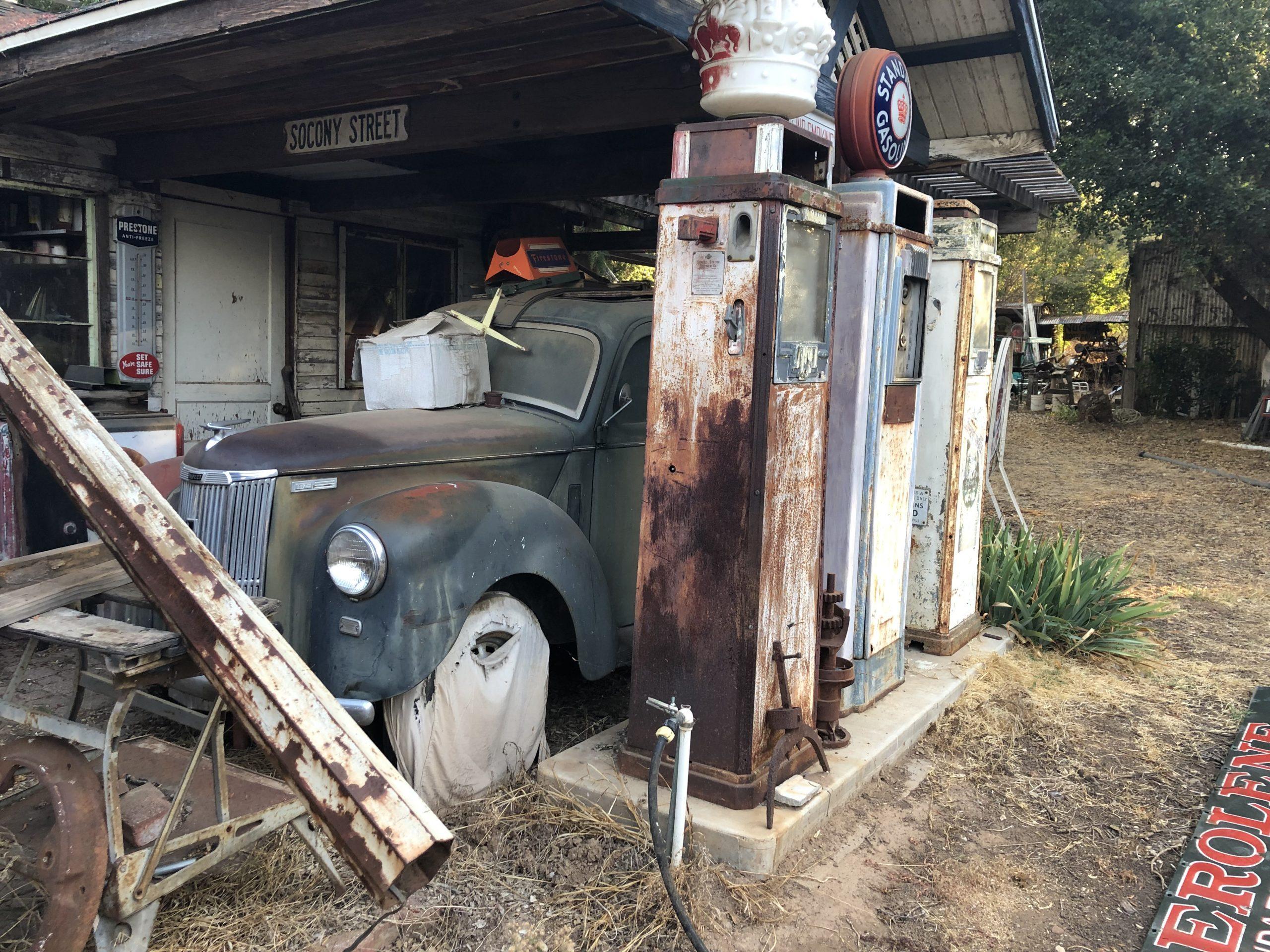 vintage car behind antique gas pumps