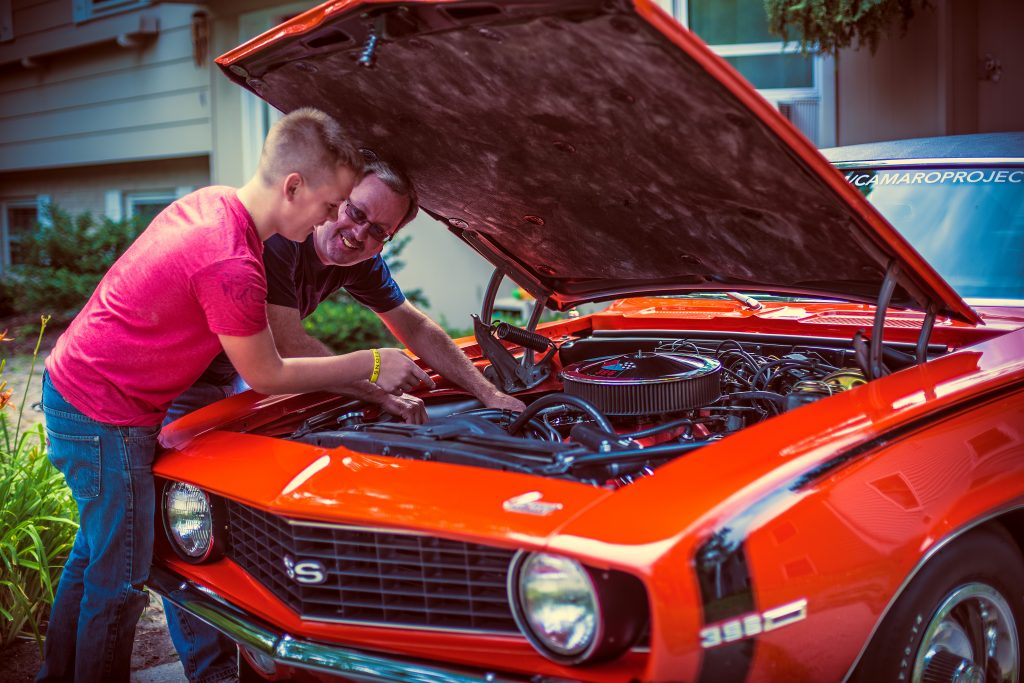 Father and Son Under Camaro Engine Bay