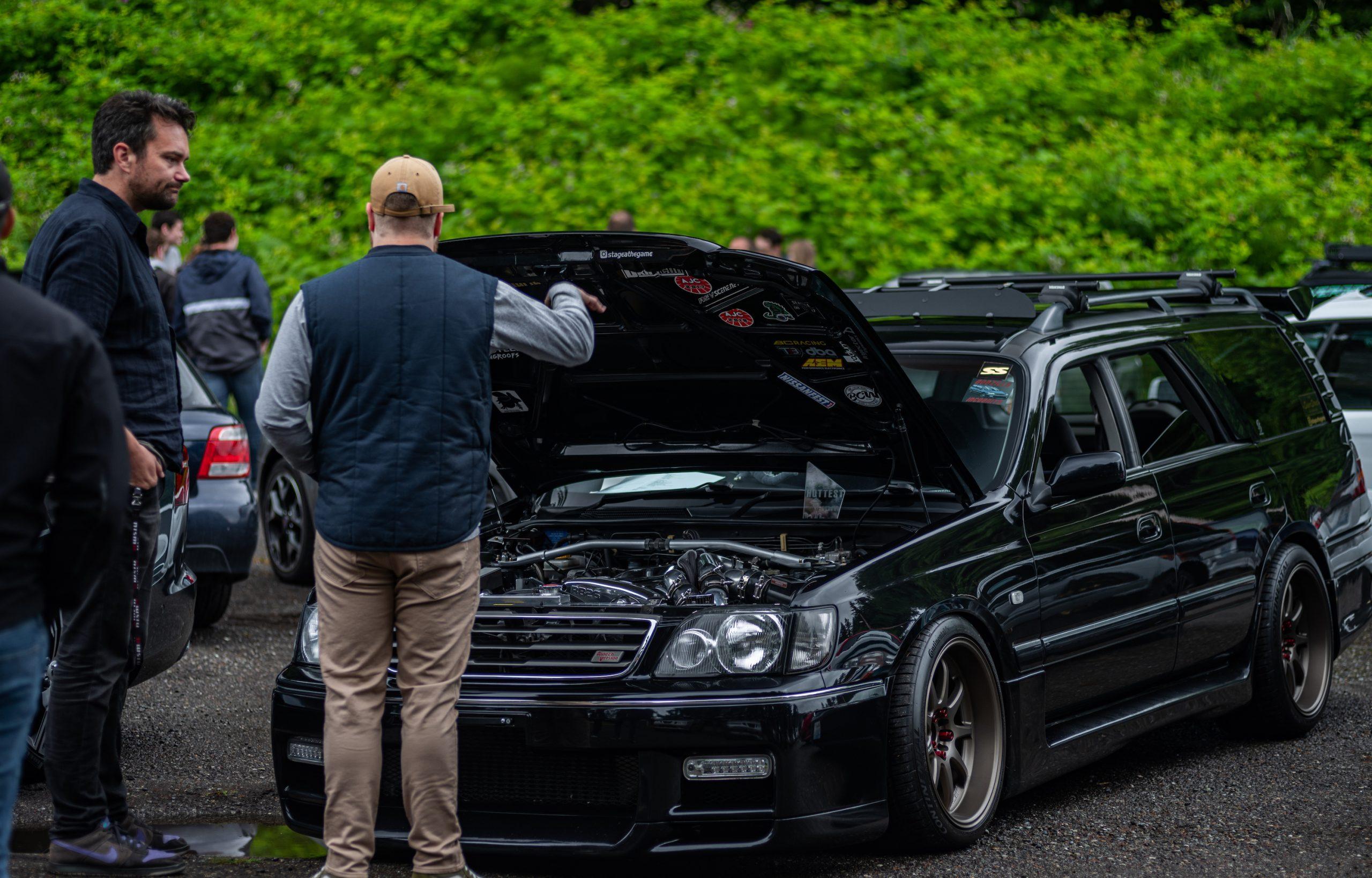 Men Talking Beside Tuner Wagon Engine Bay