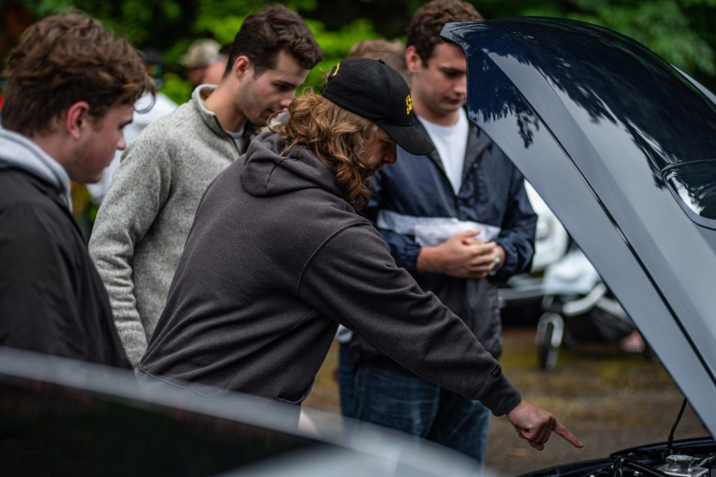 Teens Examine Engine Bay Under Open Hood