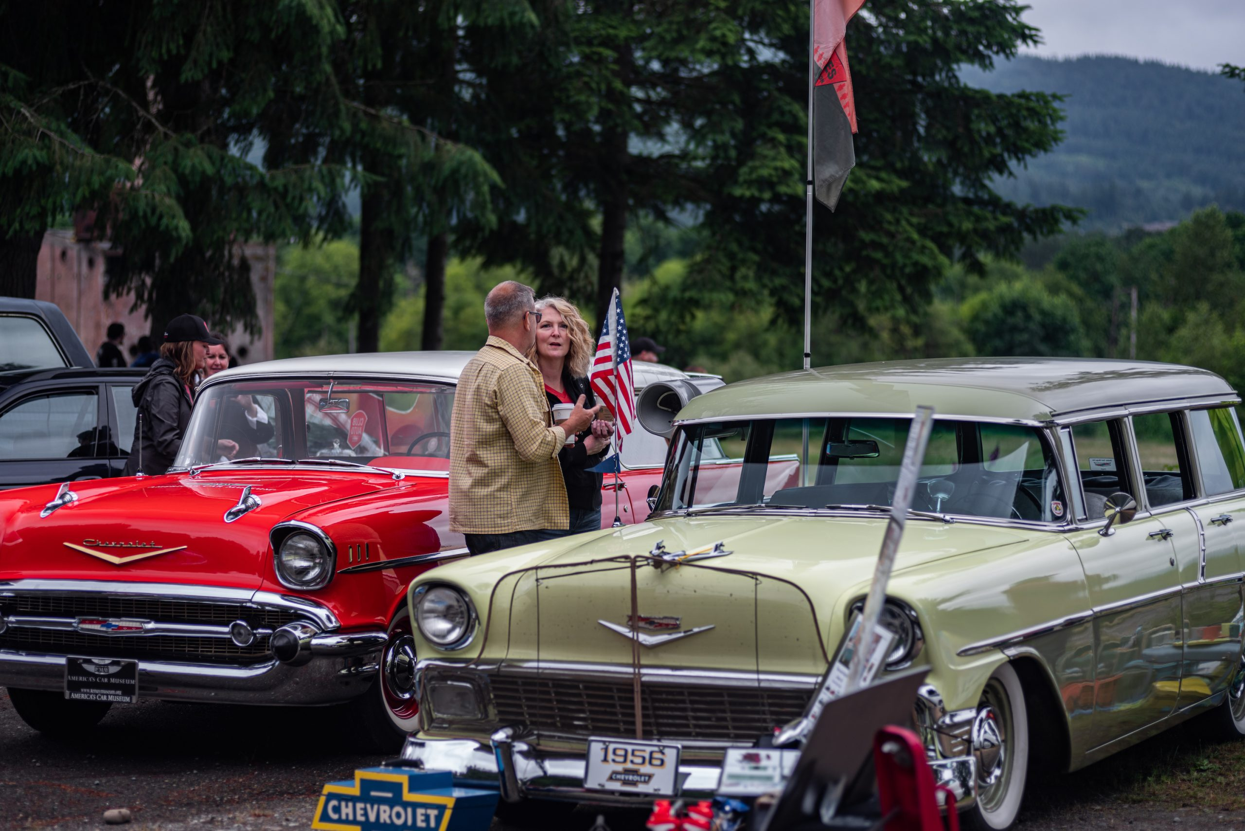 Man and Woman Chatting Between Classic Chevrolet Wagons