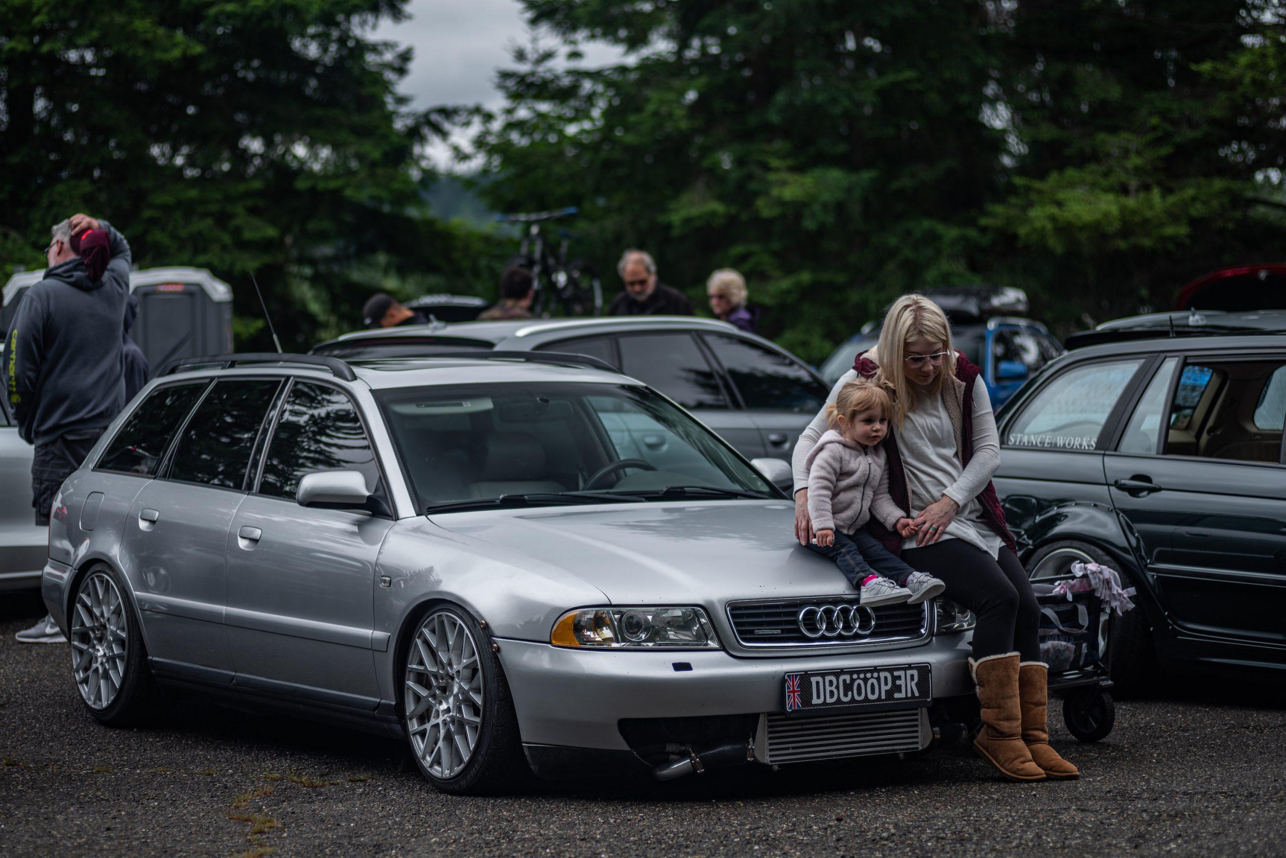 Woman and Child on Audi Wagon Hood Front Three-Quarter