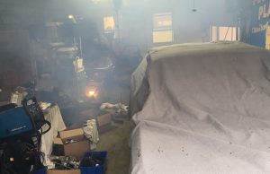 Rob Siegel - Sorting out a car - Dimly lit garage with junk