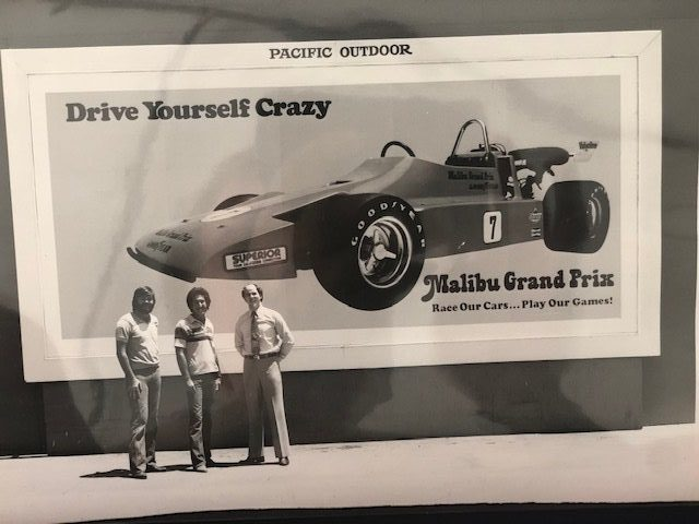 Men Standing by Malibu Grand Prix Sign