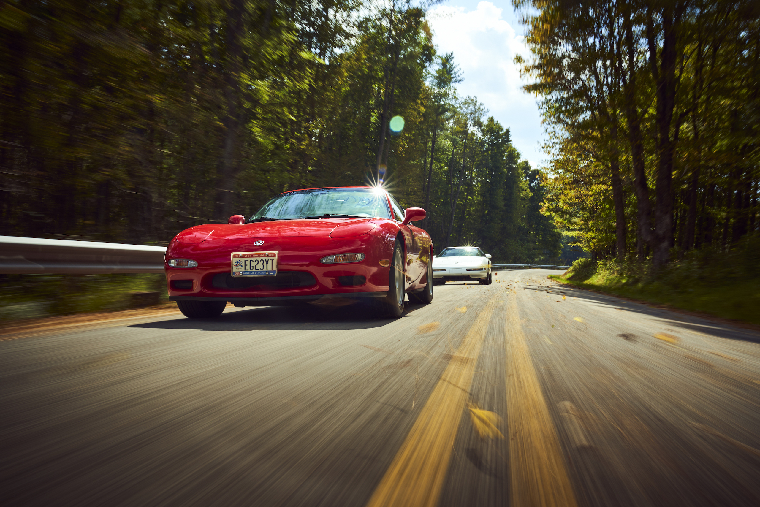 Mazda RX-7 with C4 Corvette trailing dynamic road action front
