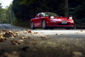 Mazda RX-7 front three-quarter dynamic road action lights up