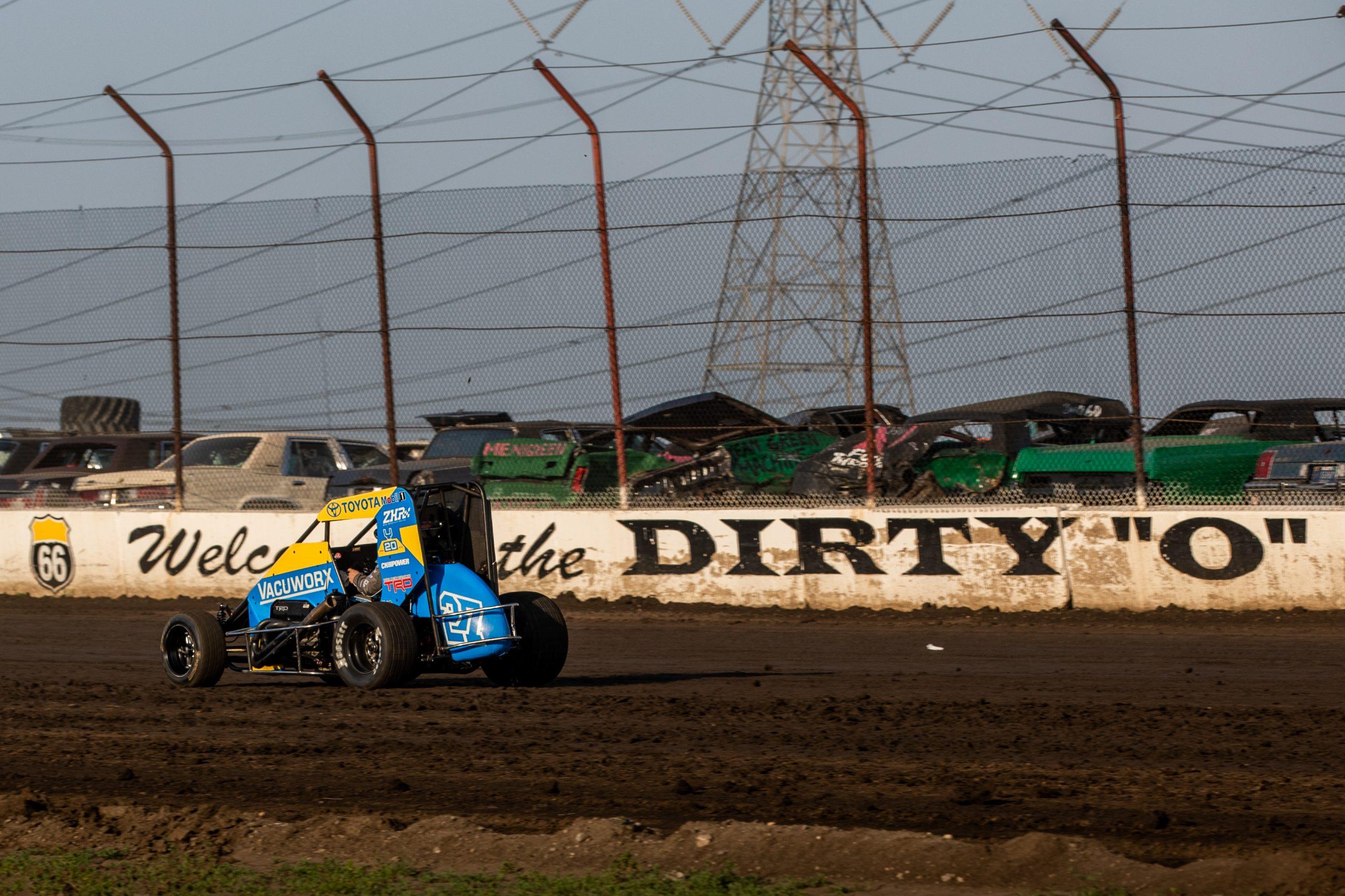 racecar dynamic rear three-quarter action on track