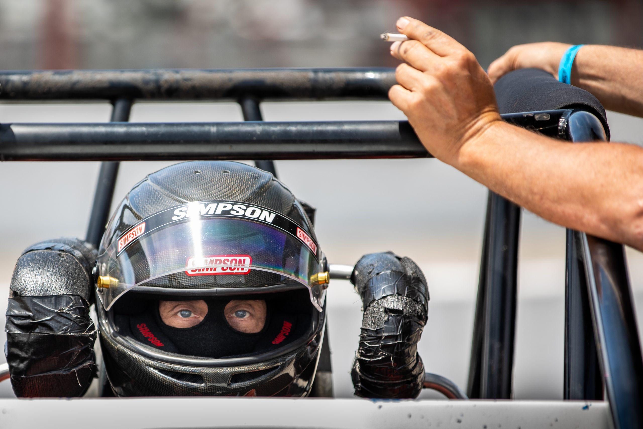racecar driver simpson ready in cockpit near cigarette pit hand