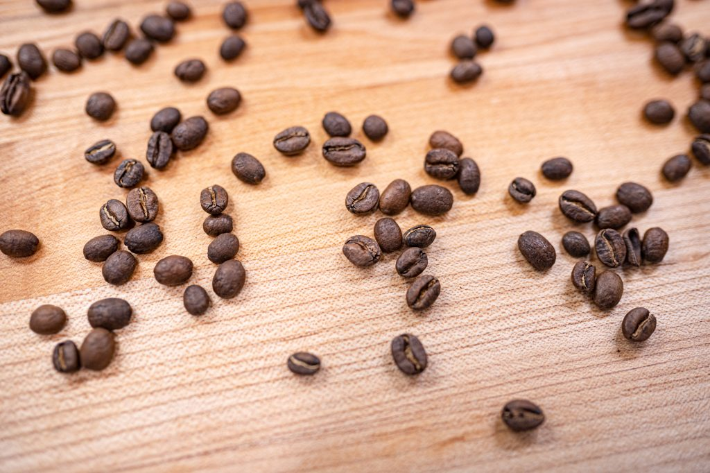 whole coffee beans on wood table close up