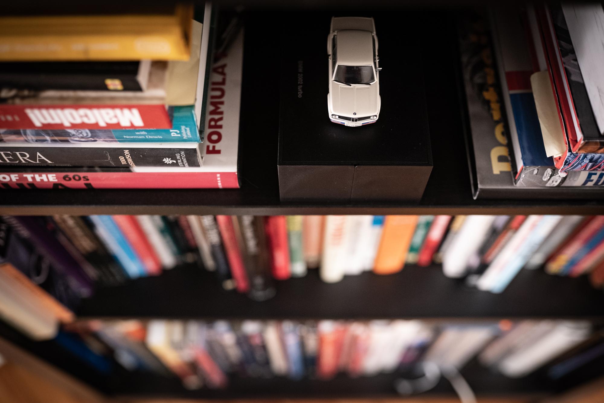 white bmw 2002 miniature on bookcase shelf