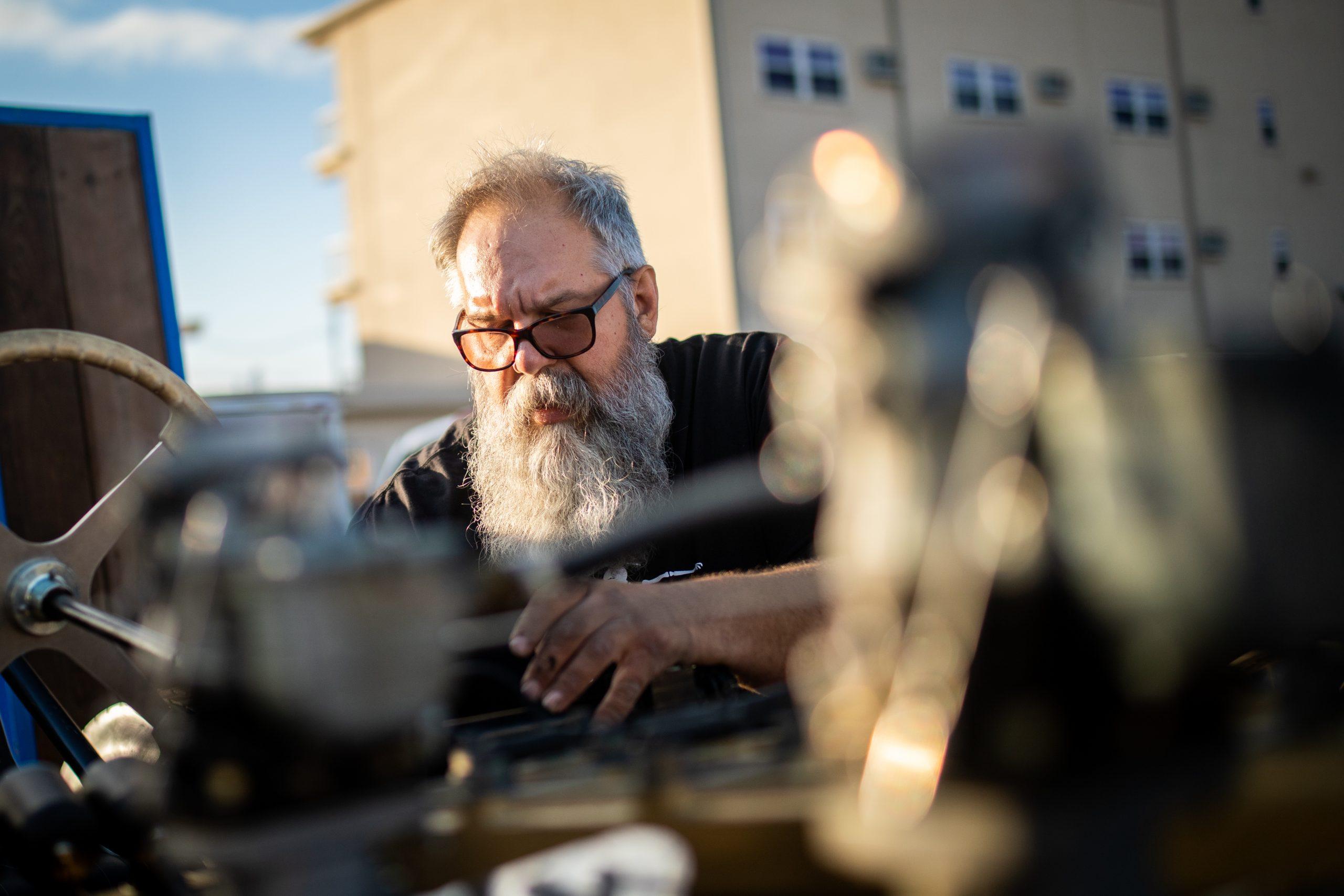 man fixing hot rod racer