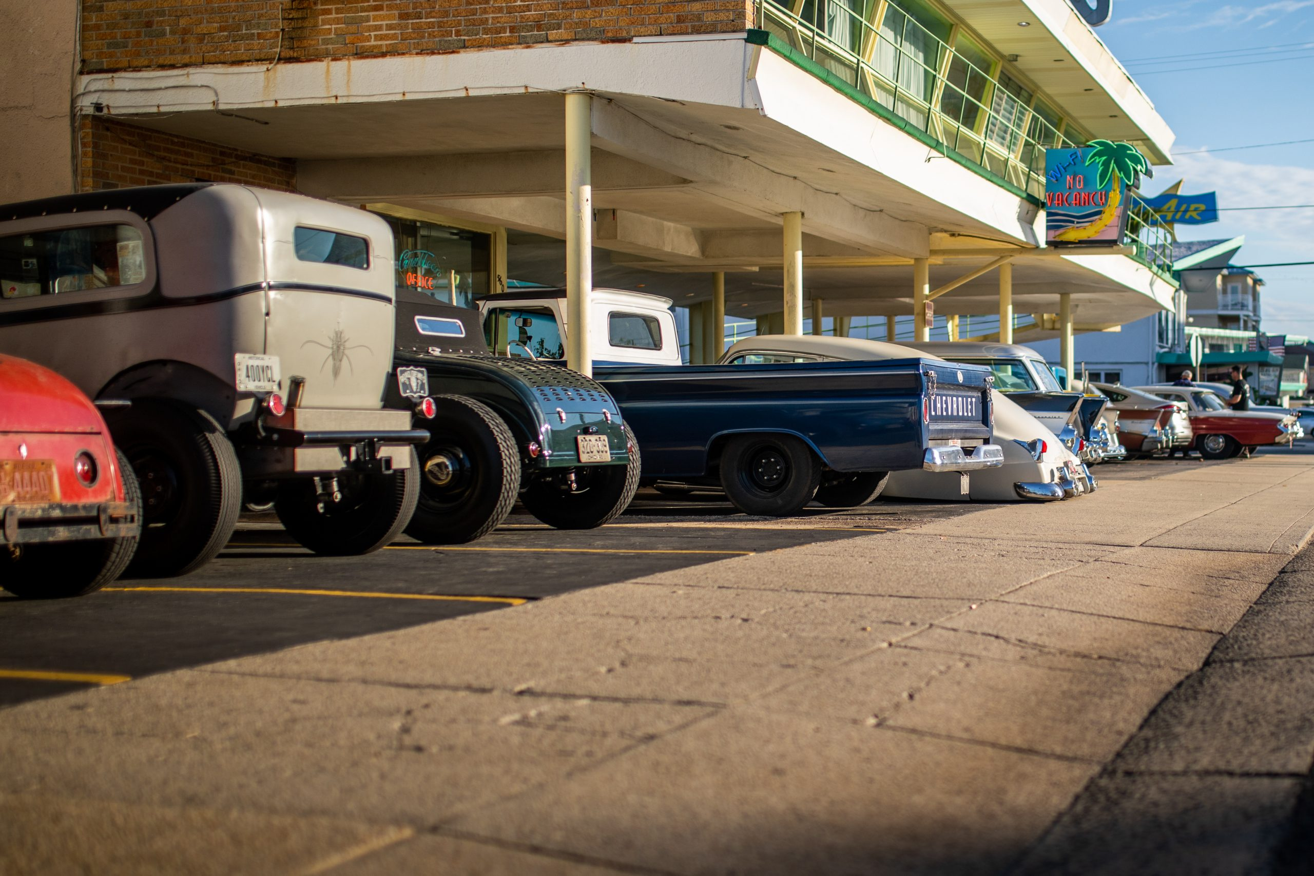 hot rods lined up under motel