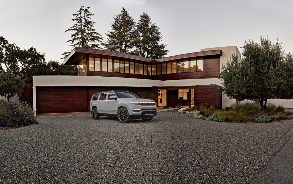 Grand Wagoneer Concept hero front three quarter in front of techno house