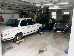 packed garage of bmw lotus vintage cars