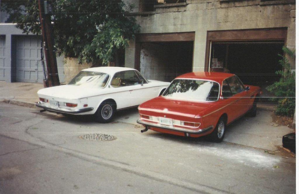 two BMW E9 coupes outside garage stalls