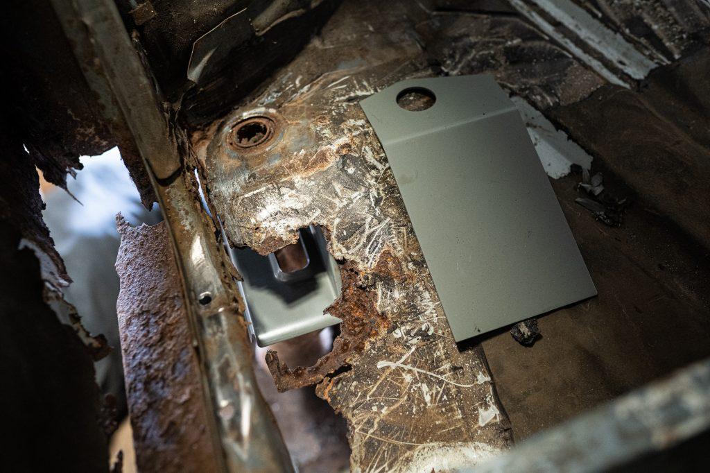 metal plate beside rotted floor of bmw 2002