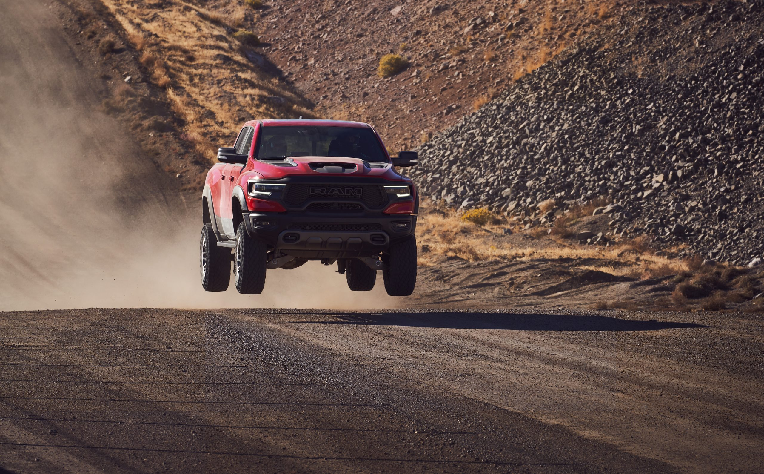 2021 Ram 1500 TRX front three-quarter dirt track dynamic action airborne red
