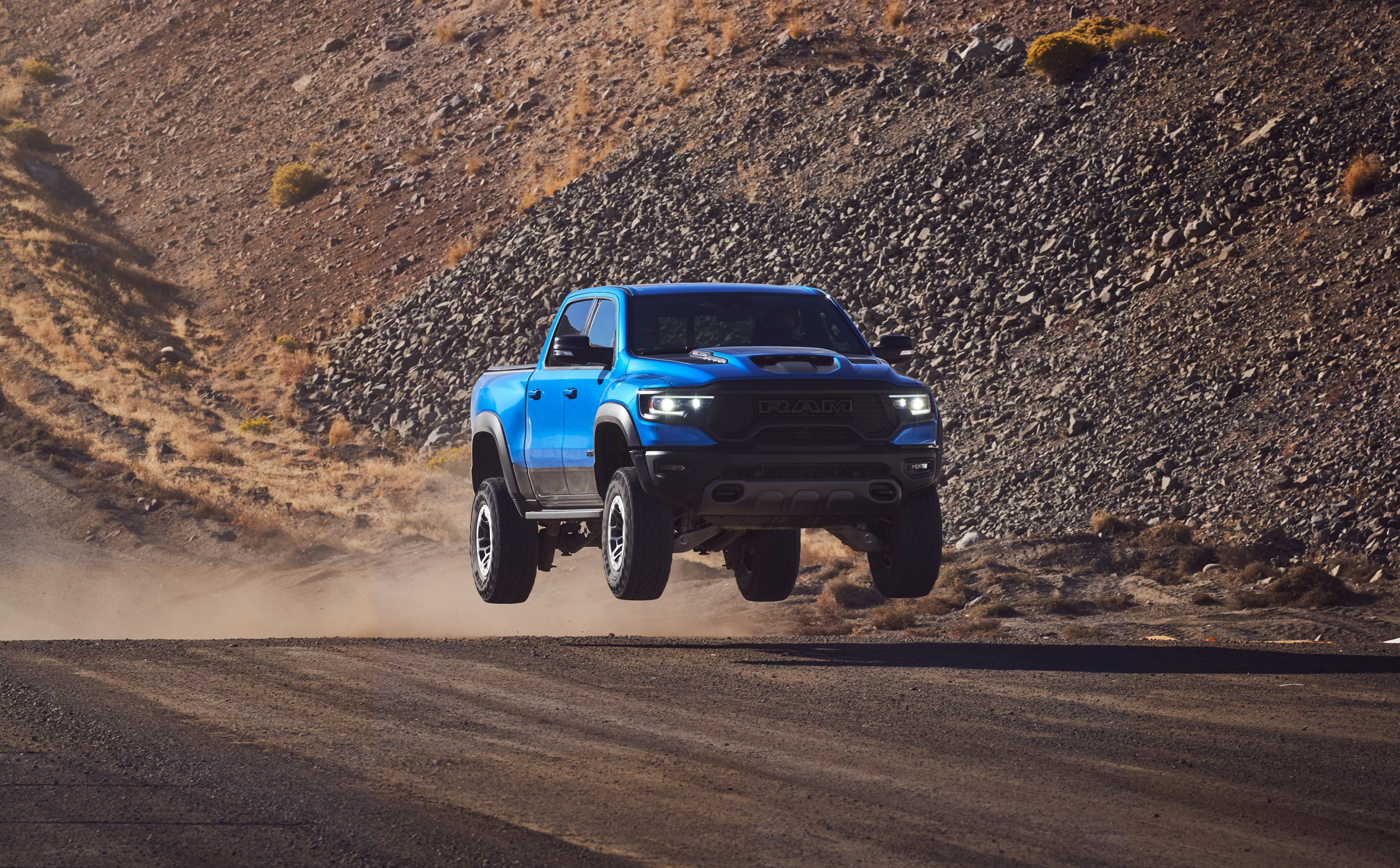 2021 Ram 1500 TRX front three-quarter dirt track dynamic action airborne blue