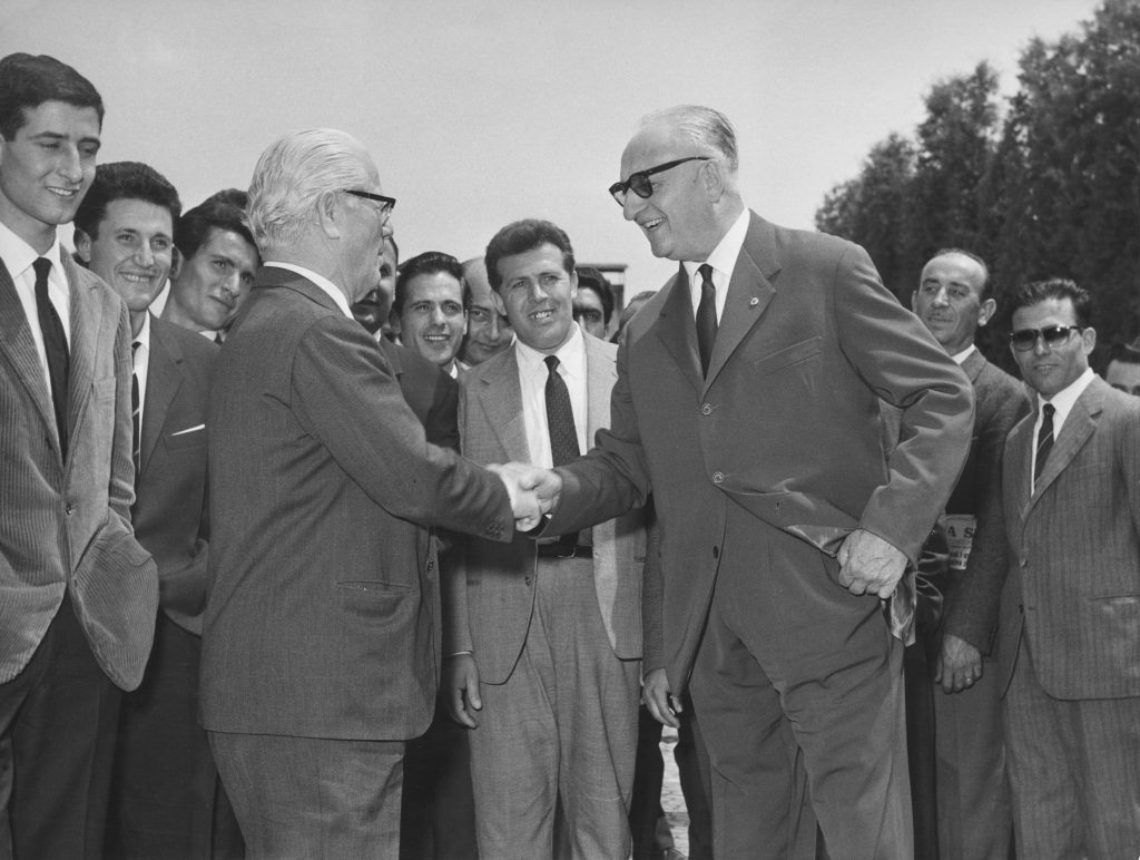 designer farina and mogul enzo ferrari shaking hands 1958