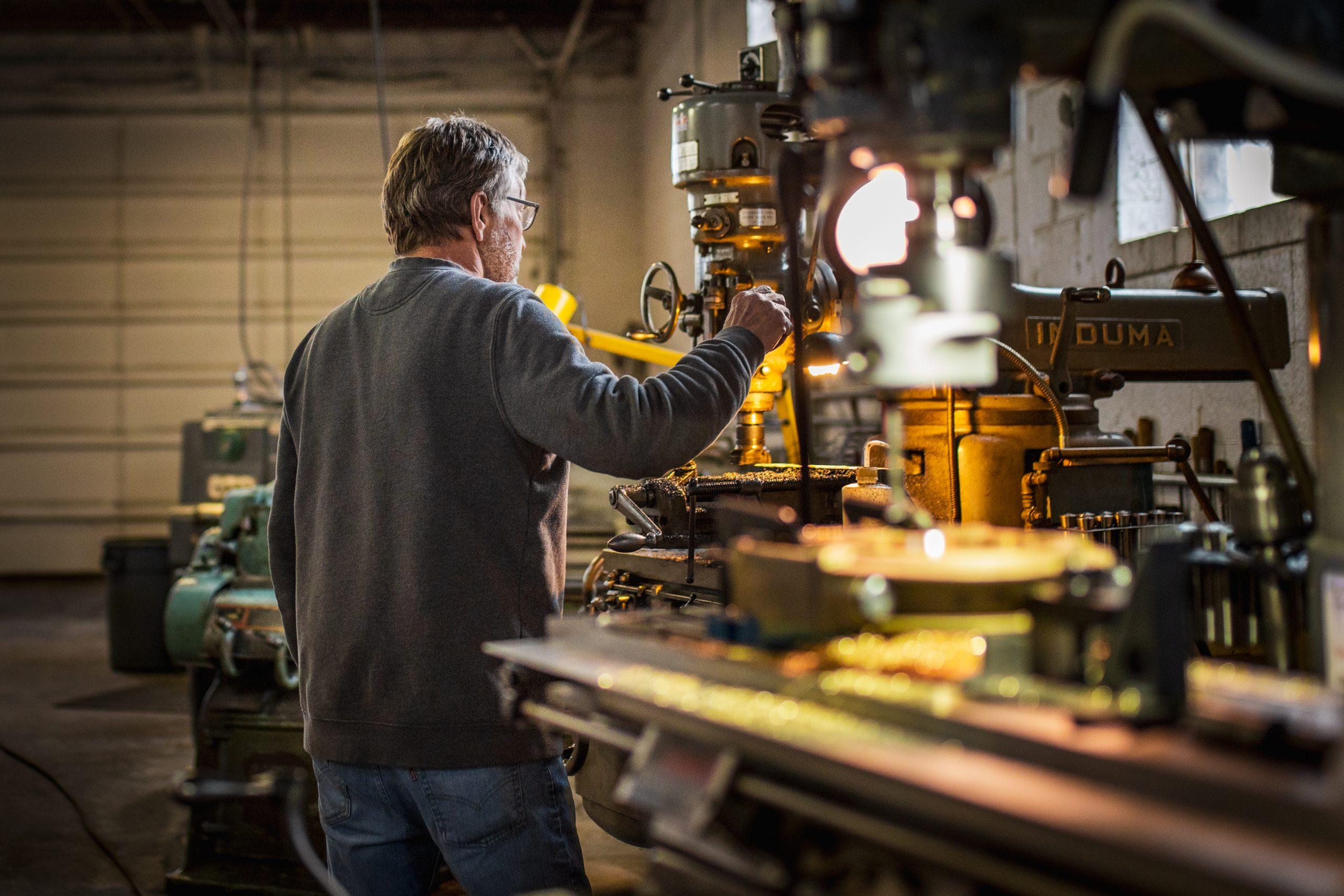 worker operates drill press