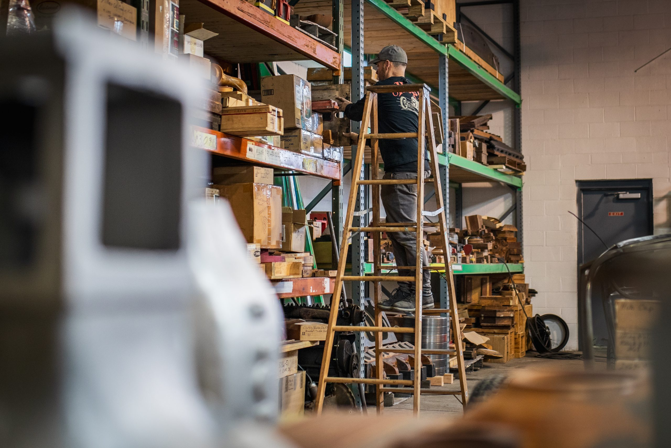worker on ladder searching shelves