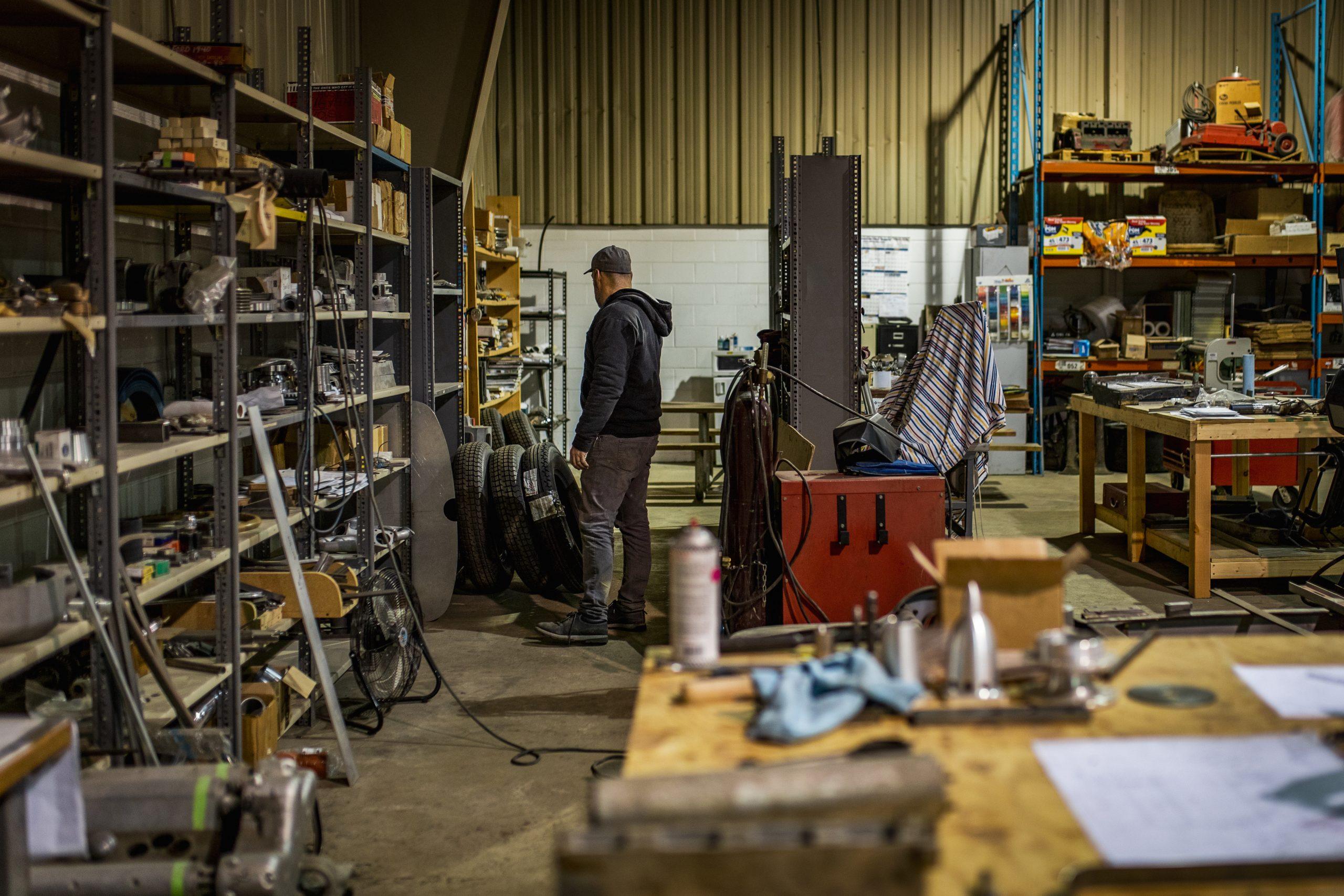 machine shop man searching shelves