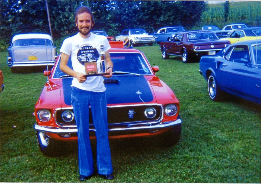 1969 Ford Mustang Mach 1 owner holding trophy