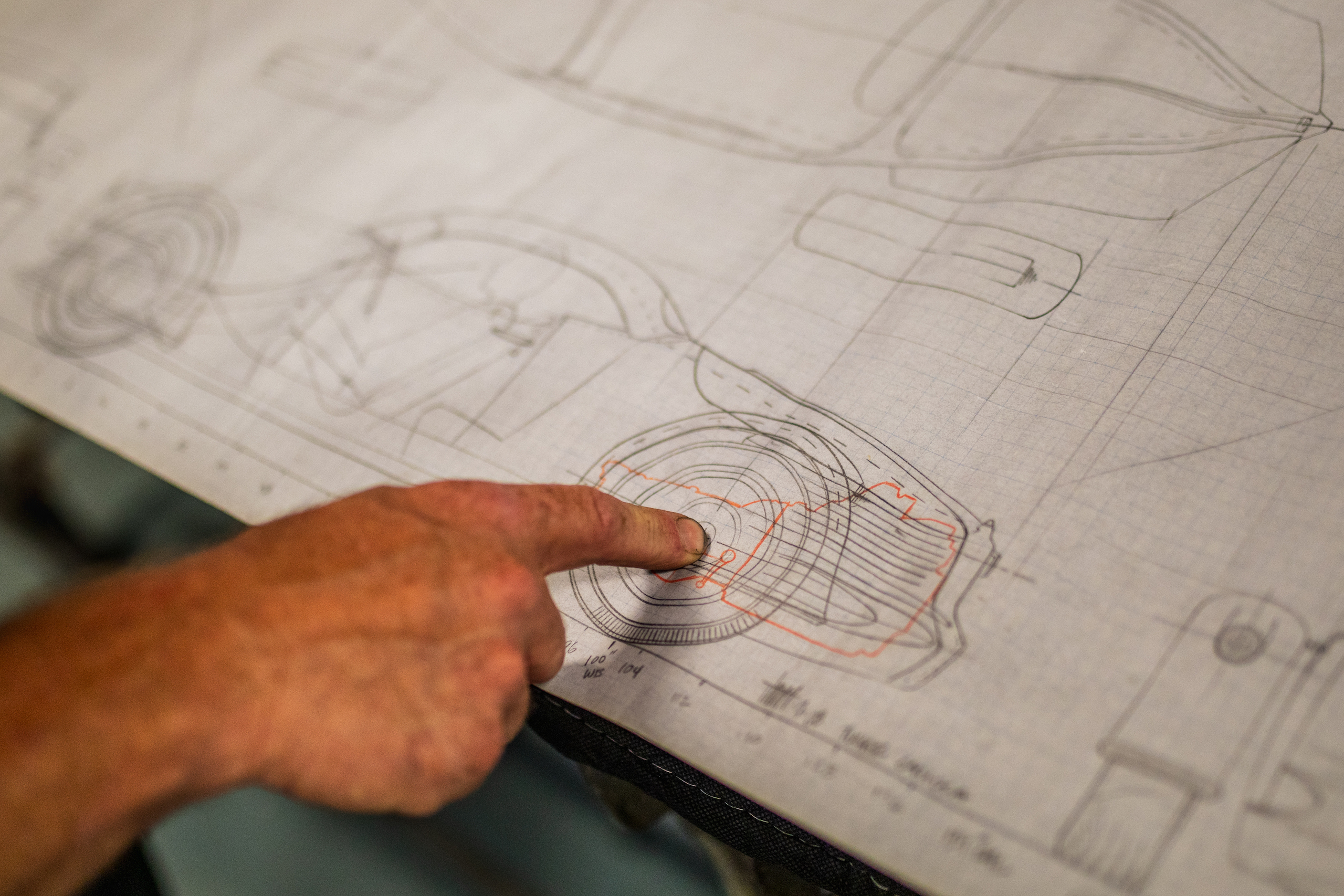 finger pointing to wheel on design drawing