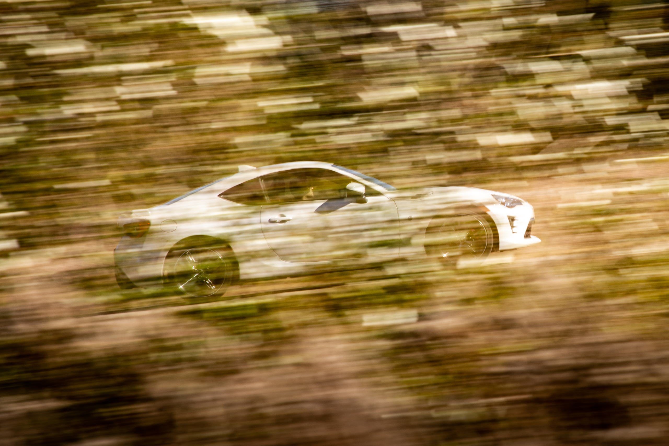 2020 Toyota 86 GT side profile dynamic action through foliage