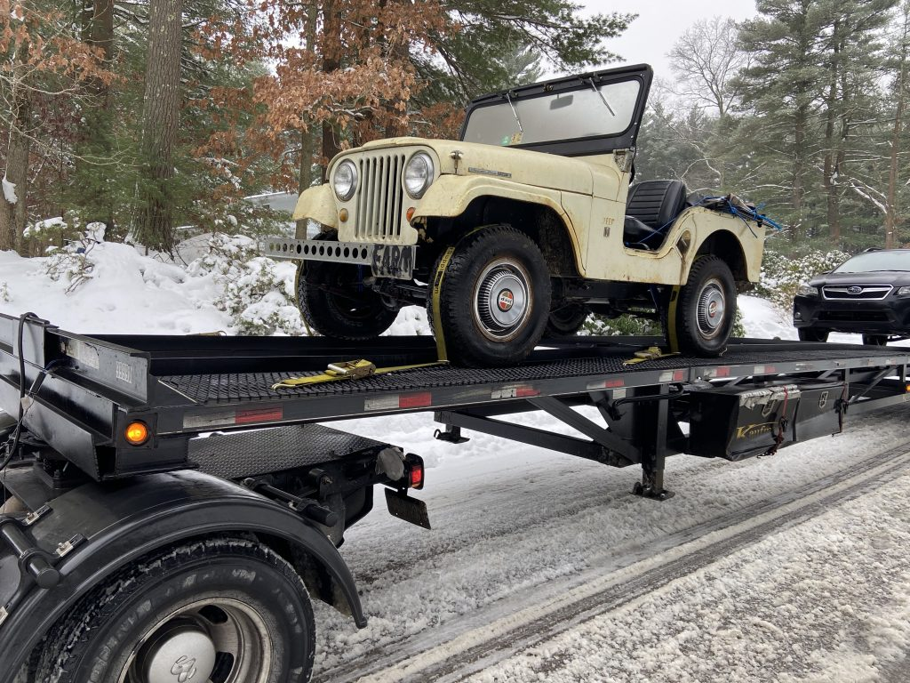 vintage jeep front three-quarter on flatbed trailer