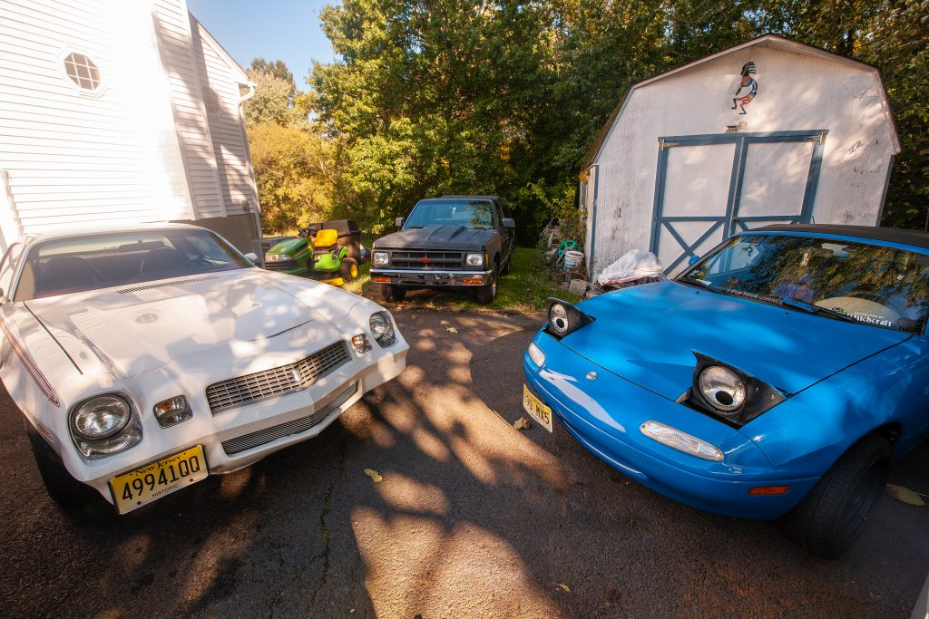 mazda and chevrolet collector cars in driveway