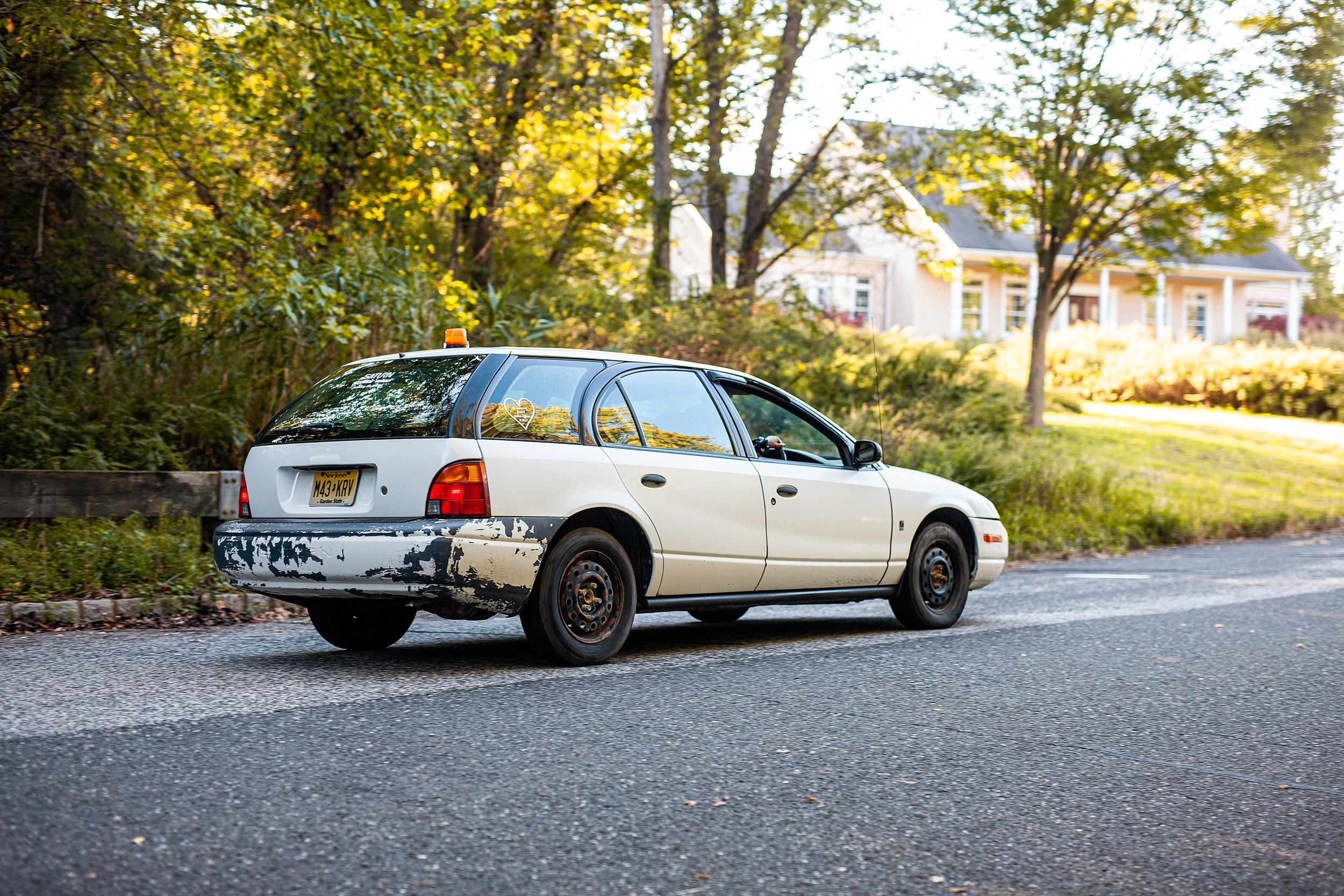 white saturn wagon rear three-quarter