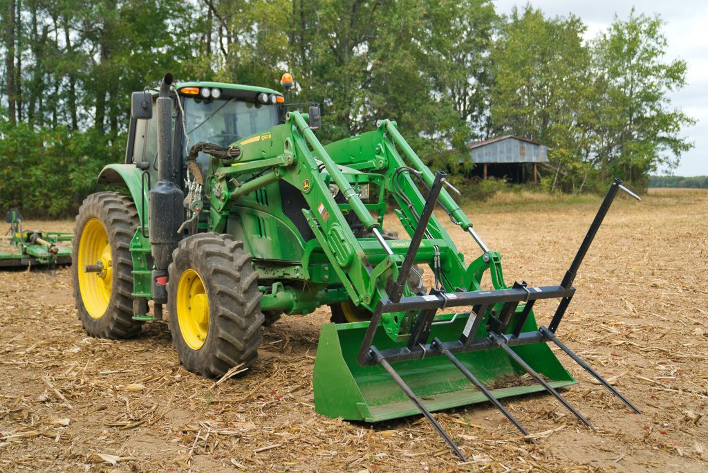 John Deere Tractor with bushhog attachment on front loader