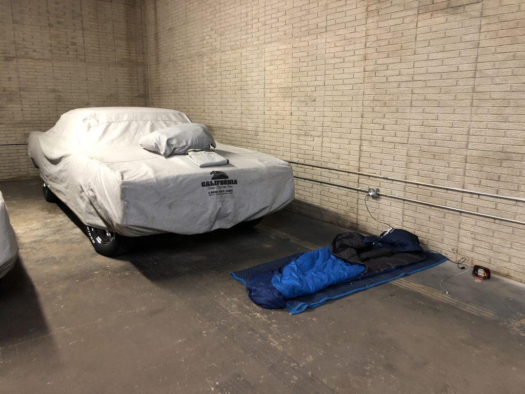 Sleeping bag in garage beside covered car