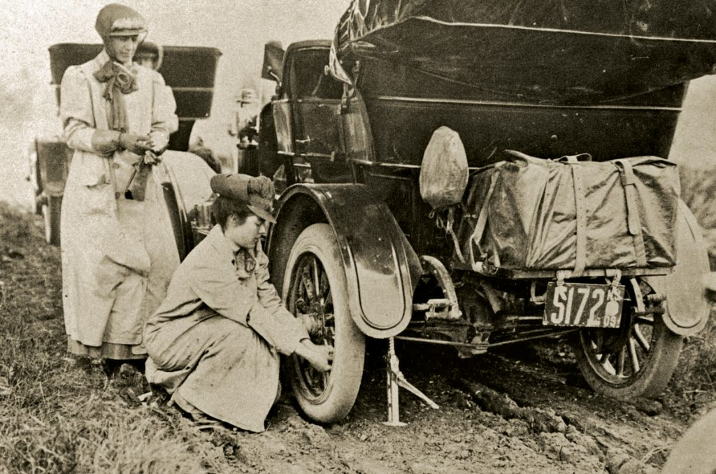 alice ramsey stops kneels changes tire on maxwell automobile