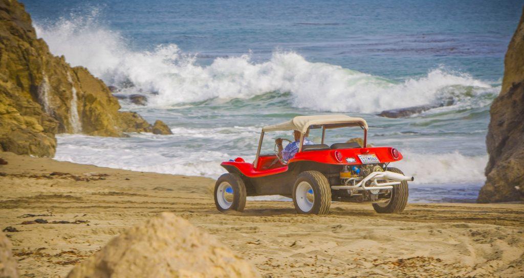 Meyers Manx Dune Buggy rear three-quarter on beach bruce at wheel