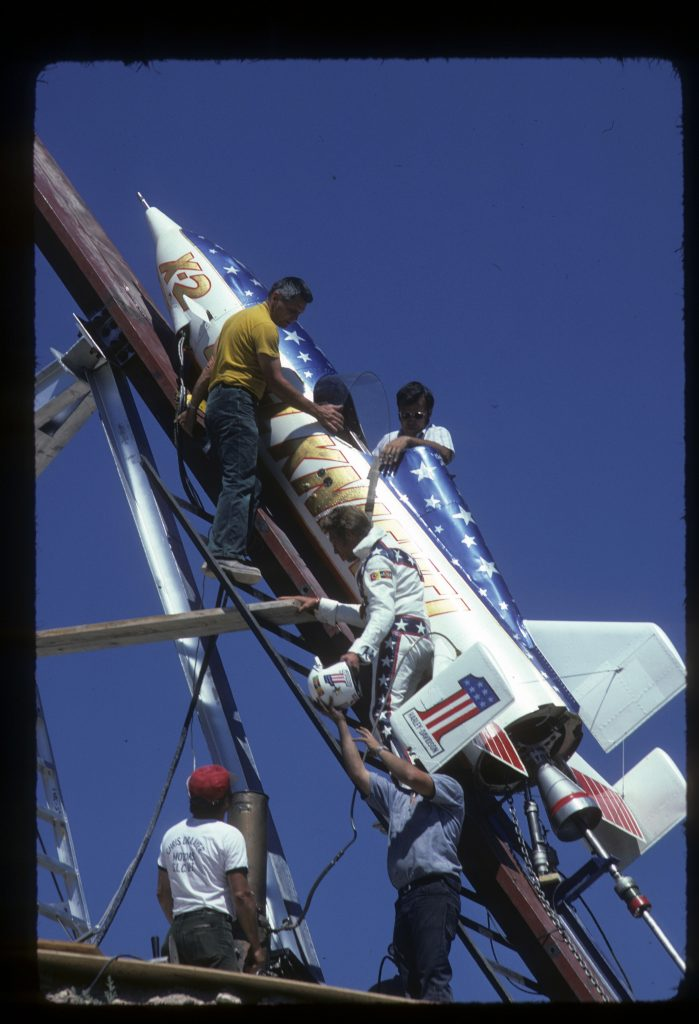 Evel Knievel with crew climbing into steam powered rocket