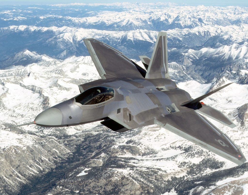 Air Force F-22 Raptor in sky over snowcapped mountains