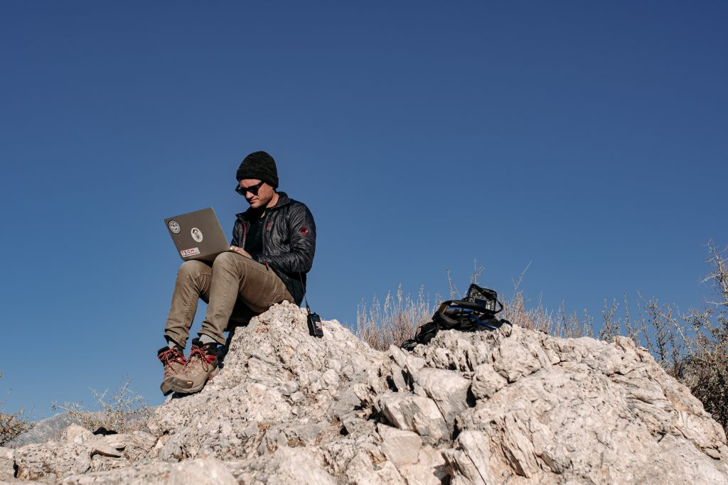 sam smith macbook and camera gear sitting on a rock