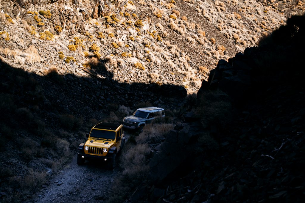 land rover defender following jeep wrangler rubicon up mountain two track