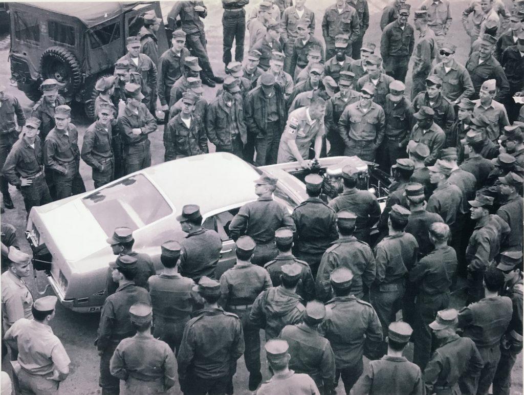 Lawman Boss 429 Ford Mustang historical military men at base surrounding car