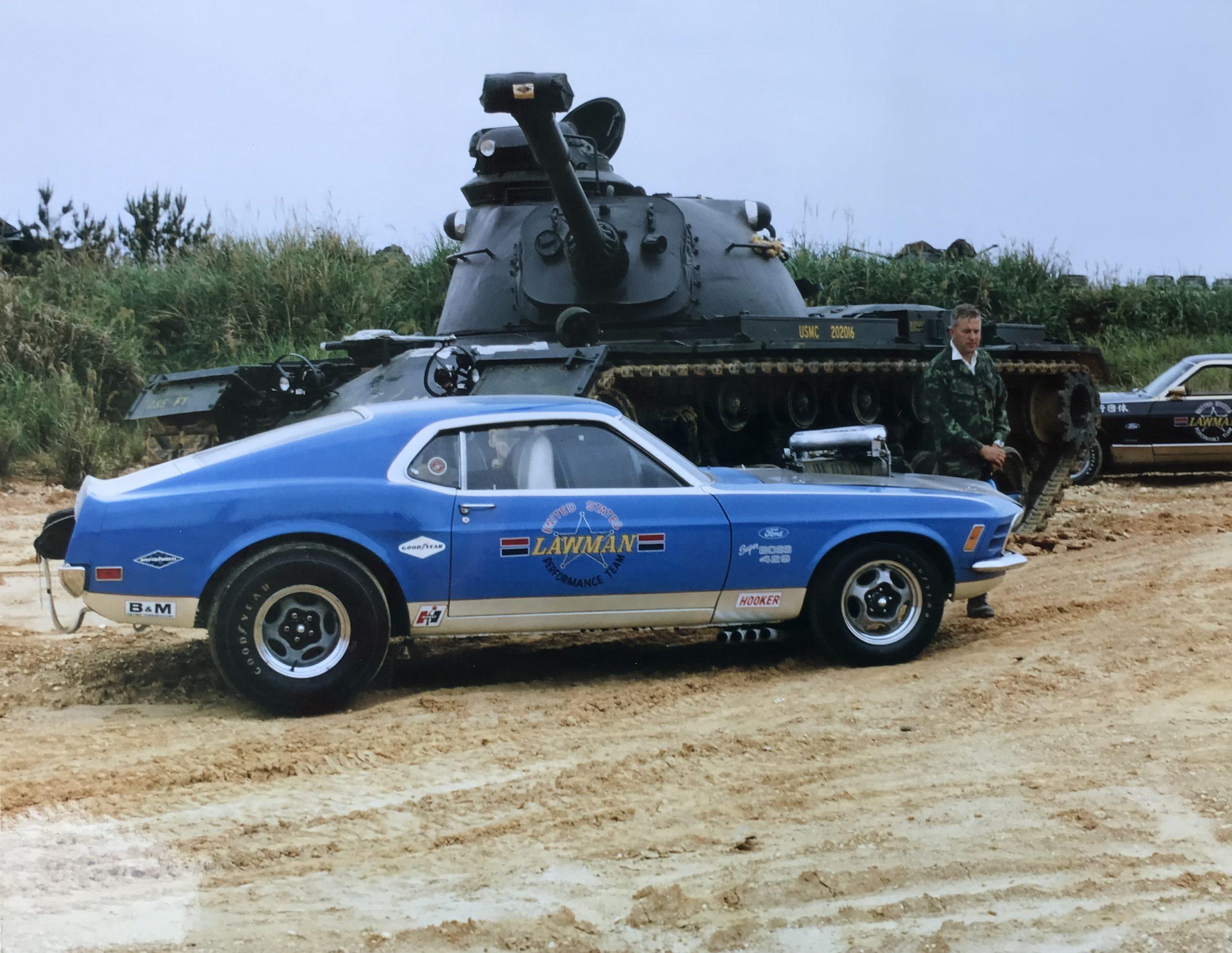 Lawman Boss 429 Ford Mustang historical car beside USMC battle tank