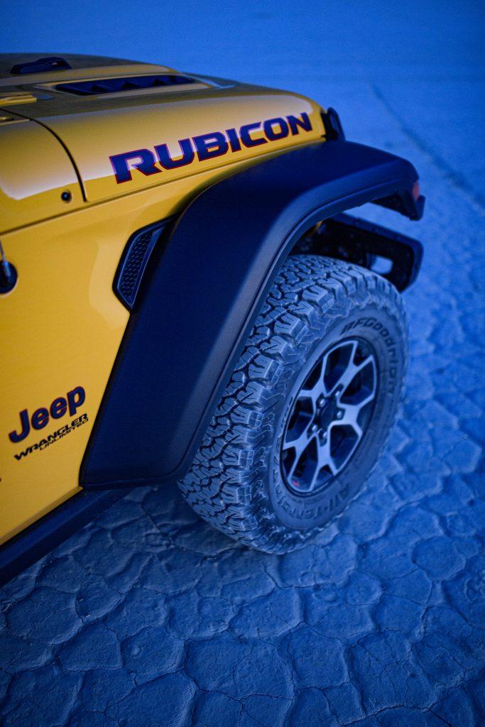 jeep wrangler rubicon front wheel and tire on blue desert floor