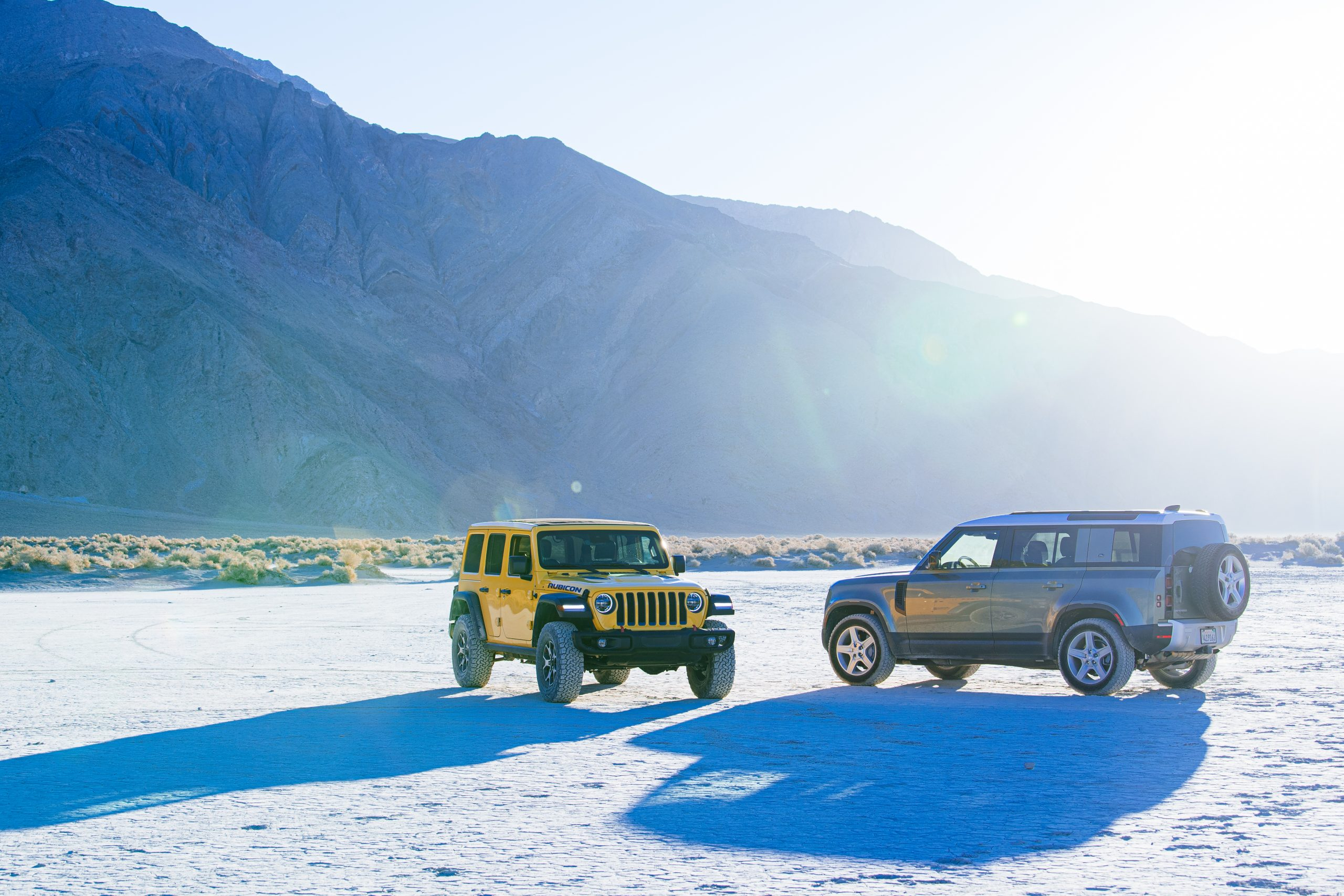 jeep wrangler rubicon and land rover defender on deserted flat