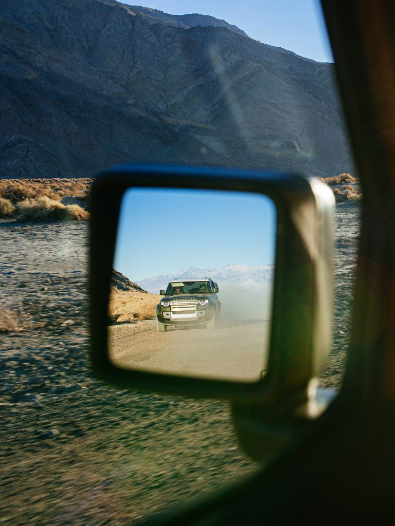 land rover defender in jeep rubicon rear view mirror vertical crop